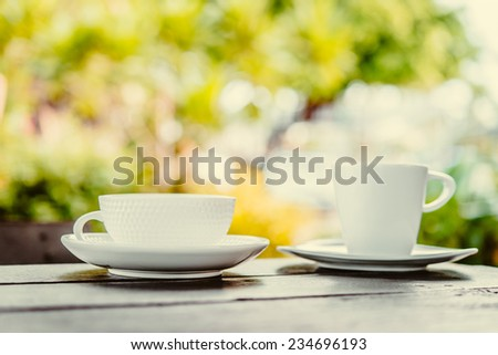 White coffee cup on wooden tables and outdoor garden background - Processing color effect style pictures