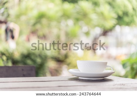 White coffee cup on wooden tables and outdoor garden background - Processing color effect style pictures - stock photo