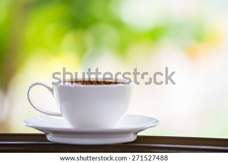 White coffee cup placed on the window sill. - stock photo