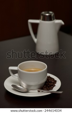 White coffee cup with beans beside pot - stock photo