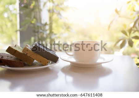 White coffee cup with bread plate on the table with sunlight in the background.