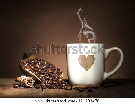 White coffee cup with heart and wooden spoon with coffee beans on wooden and brown background. - stock photo