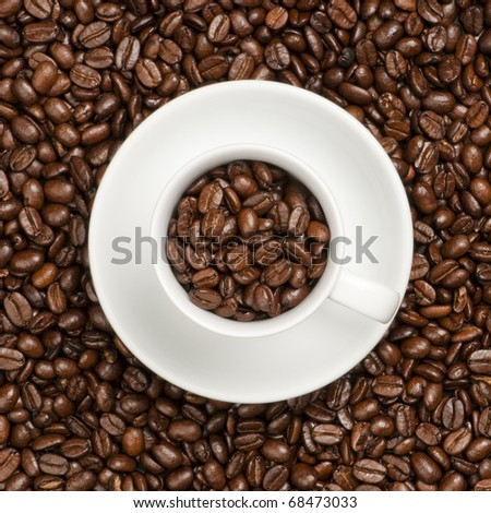 White coffee cup with plate and coffee beans.