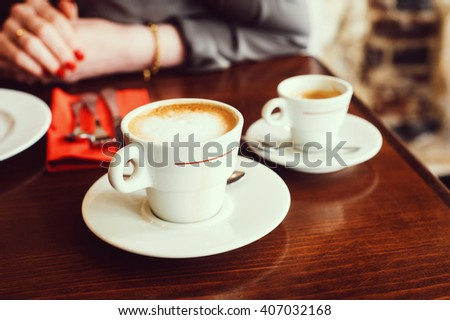 White coffee cups in Parisian indoors cafe - stock photo