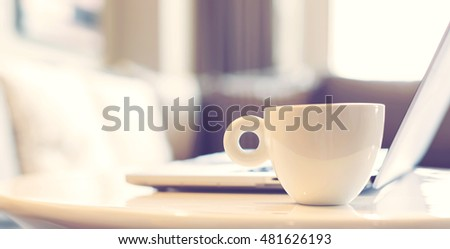 White coffee mug beside laptop computer for early morning work concept