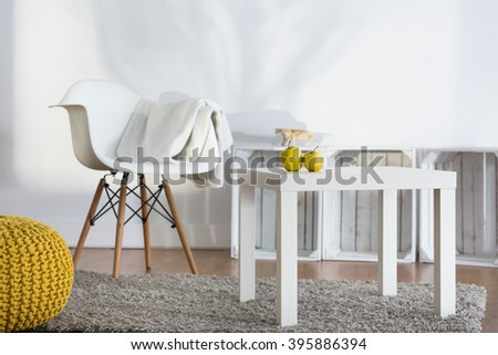 White coffee table and armchair in modern spacious living room with contemporary decor - stock photo