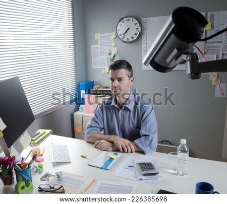 White collar at office desk working with surveillance camera on foreground. - stock photo