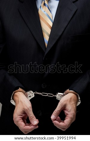 White collar criminal in a business suit and handcuffs - stock photo