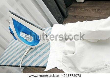 white collar shirt and iron on ironing board - stock photo