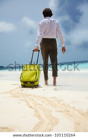 White-collar worker on the beach vacation - walking with green suitcase - stock photo