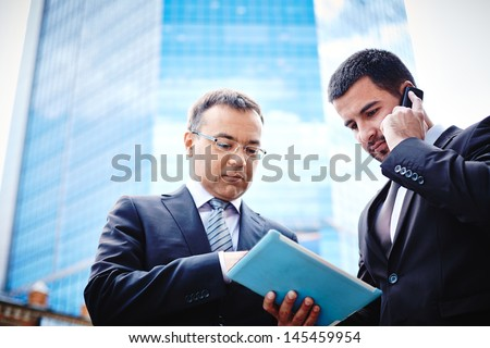 White-collar workers being busy with the project and consulting via mobile - stock photo