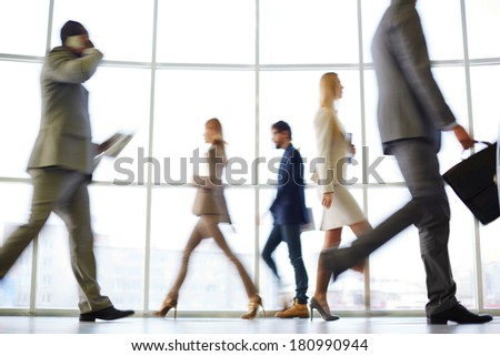 White collar workers going down office corridor at the end of working day - stock photo
