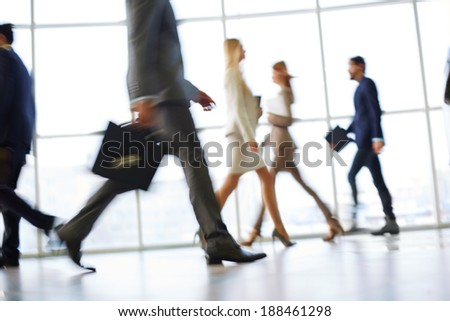 White collar workers going down office corridor during working day - stock photo