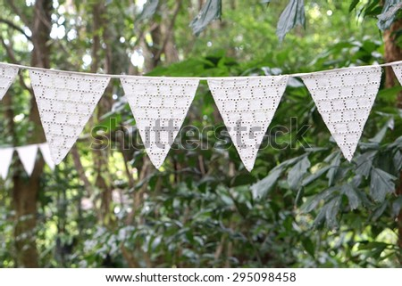 White color vintage style fabric triangle decortation party flag hanging with nature background