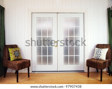 white colored french doors in a room bordered by rattan chairs - stock photo