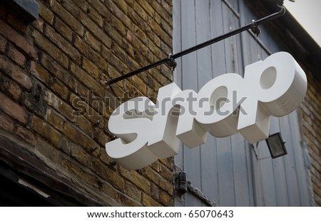 White coloured shop sign in front of a trade building - stock photo