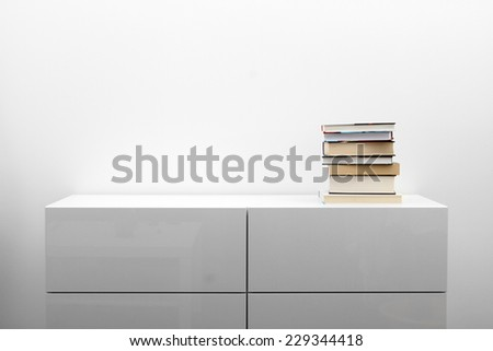 white commode with stack of books in bright minimalism interior - stock photo