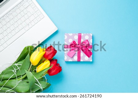 White computer and bouquet of tulips with gift on blue background - stock photo