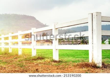 White concrete fence in farm field - stock photo
