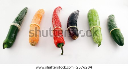 White condoms on different vegetables: pepper, carrot,  egg-plant, cucumber