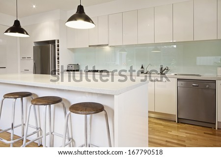 White contemporary kitchen with island and bar stools