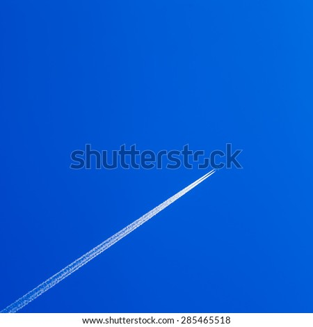 White contrail trace of plane on clear blue sky. - stock photo