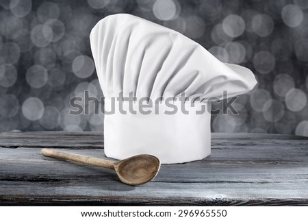 white cook hat spoon of wood and blue desk top