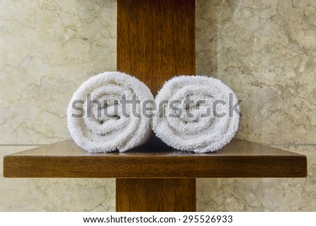 White cotton hotel towels on wooden cross