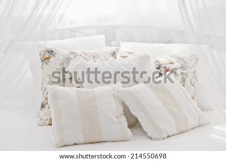 White cozy bed with vintage pillow - stock photo