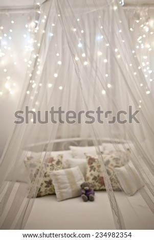 White cozy bed with vintage pillow and Christmas lights, defocused - stock photo