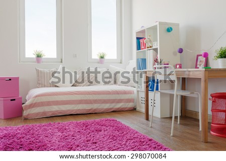 White cozy children room with wooden floor and pink carpet - stock photo