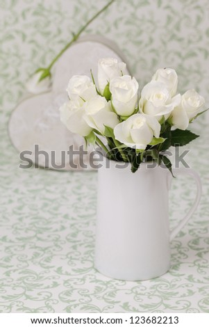 White cream roses in a vase with heart shaped gift box.