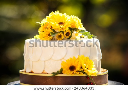 white creamy delicious cake decorated with yellow flowers and green leafs