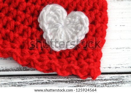 White crochet heart on a red baby hat - stock photo