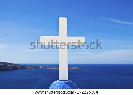 White Cross, a cross on top of a church at Santorini, against the Aegean blue - stock photo