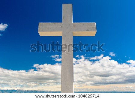 White cross against blue sky and fluffy clouds - stock photo