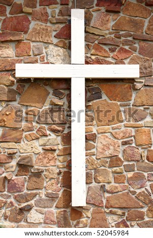 White cross on rock wall - stock photo