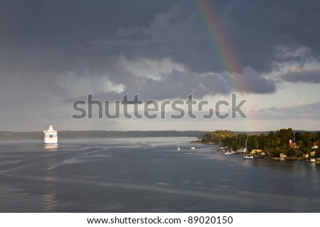 white cruise liner and rainbow in rain during sunshine in Baltic sea - stock photo