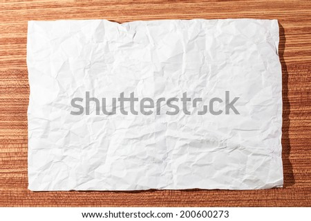 White crumpled paper on a wooden floor.