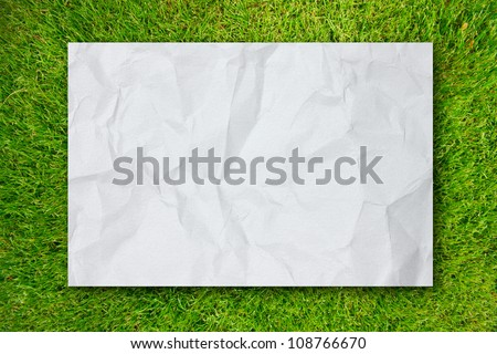 White Crumpled paper on Green grass background - stock photo