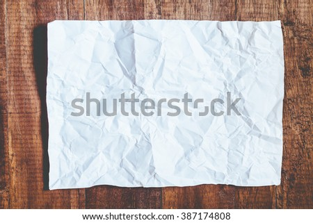 White crumpled paper on wood background