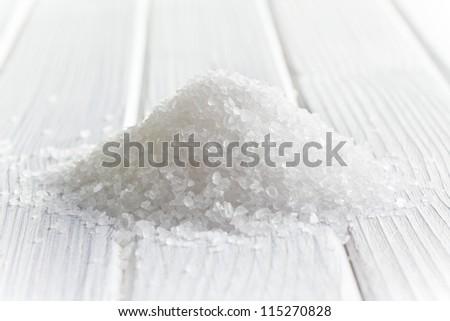 white crystal salt on wooden table - stock photo