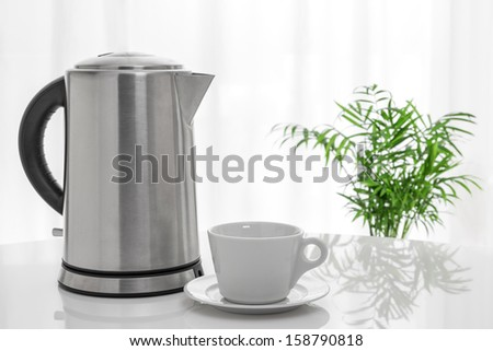 White cup and electric kettle on the table, with green plant in the background. - stock photo
