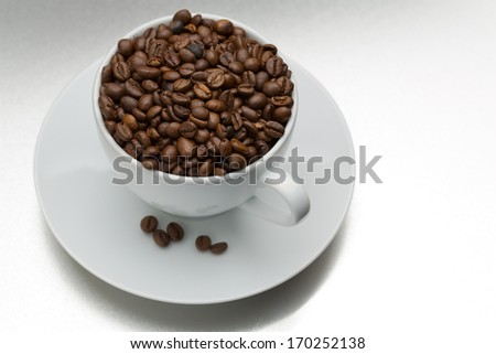 White cup and saucer full of coffee beans on textured steel surface