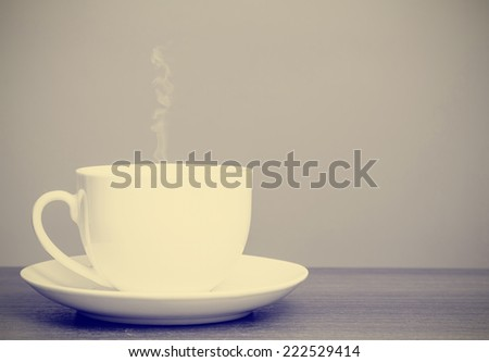 White cup and saucer on wooden table with retro filter effect - stock photo