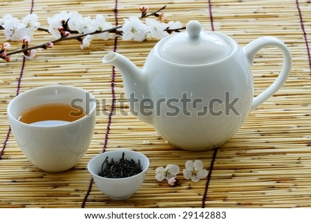 White cup and teapot on bamboo straws