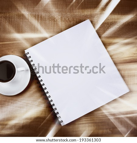 White cup and white page on wooden table