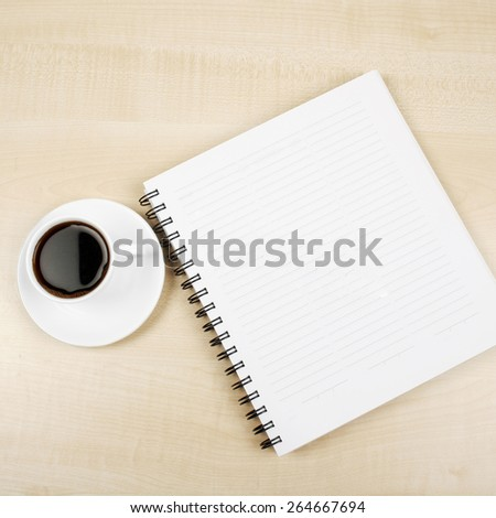 White cup and white page on wooden table - stock photo