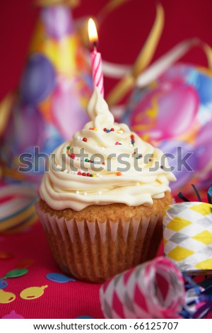White cup cake with candies on top and candle on red background