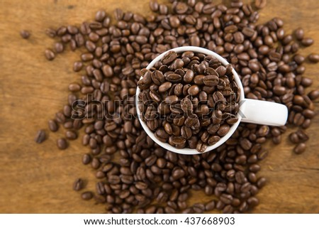 White cup full of coffee beans on Roasted Coffee Beans and wood background, top view.jpg